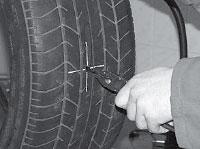Захватываем плоскогубцами кончик ножки грибка и выводим ее на поверхность шины.