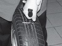Ремонт сквозных повреждений бескамерных шин, располагаем кончик шила со вставленным жгутом напротив отверстия.
